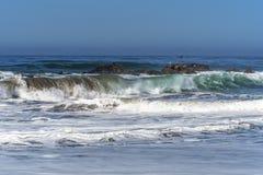 Waves splashing on huge rocks, off shore, Royalty Free Stock Photos