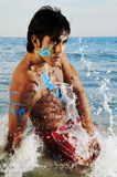 Waves splashing on male model. Waves splashing on hispanic male model on the beach wearing artistic bodypaint drawing Royalty Free Stock Photography