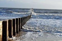 Waves splashing over groynes Stock Photos