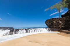 Waves splashing over lava rock on beautiful sandy tropical beach stock photo