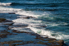Waves splashing over rocky coast in australia. A set of waves are rolling in and splashing over the rocky coast of an australian beach Stock Photo