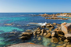 Waves splashing rocks at Bay of Fires in Tasmania, rocky coastli. Waves splashing rocks at Bay of Fires in Tasmania. Colorful fiery red orange lichen growing on Stock Photos