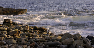 Waves Splashing in on Rocks on a warm summer evening. Rough Waves splash into a rocky beach on a summer evening as the sun goes down and blasts golden light onto stock photography