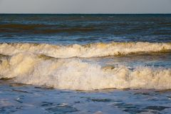 Waves splashing on the shore spot on focus stock images