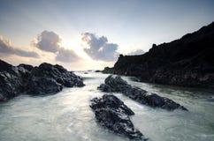 Waves splashing on the unique rocks formation over beautiful sunrise background Stock Photos