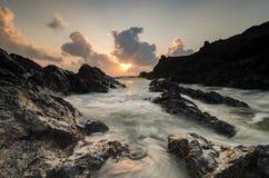 Waves splashing on the unique rocks formation over stunning sunrise background Stock Image