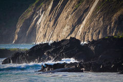 Waves splashing on volcanic rocks in the Royalty Free Stock Photography
