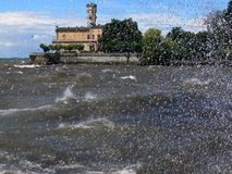 Water castle in the storm. Waves and spray at the lake, churned lake at the Castle, royal building on the lakeshore, Landscape on the lake after the storm, Water Royalty Free Stock Photos