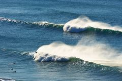 Waves spraying and surfers. On the sea stock images