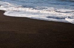 Waves spread on black sand beach Stock Photo