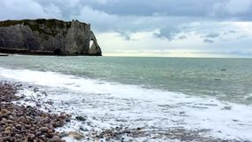 Waves on a stone beach near a rock in cloudy sky backdround.  stock video footage