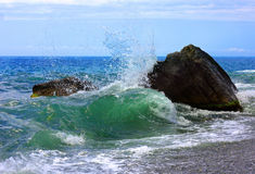Waves, stone and sea foam Stock Photos