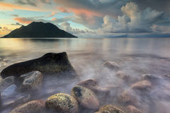 Beautiful Waves and stones. Serenity and peaceful evening at Maitara, Ternate, Moluccas Indonesia with volcano as background Royalty Free Stock Image