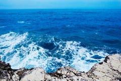 Waves on the Stony Coast. The waves breaks on the stony beach with splash and foam Royalty Free Stock Image