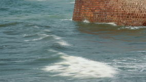 Waves strike the stone wall stock video