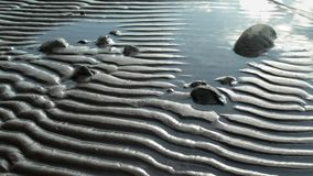 Waves on a striped beach. Striped patterns in the sand created by wind and waves stock video