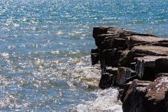 Waves on sunny day splashing against breakwall Royalty Free Stock Images
