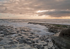 Waves in the Sunrise. Sunrise on a rocky beach with tide slowly making its way in as the waves gently rub against the rocks royalty free stock image