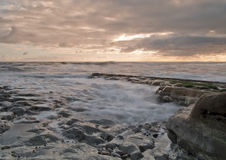 Waves in the Sunrise. Sunrise on a rocky beach with tide slowly making its way in as the waves gently rub against the rocks stock photography