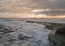 Waves in the Sunrise. Sunrise on a rocky beach with tide slowly making its way in as the waves gently rub against the rocks stock image