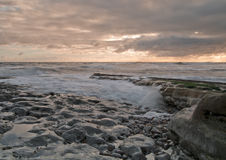 Waves in the Sunrise. Sunrise on a rocky beach with tide slowly making its way in as the waves gently rub against the rocks royalty free stock photography