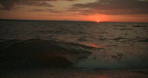 Waves at sunset in slow-motion, pan up from water to sky at 25 fps stock footage