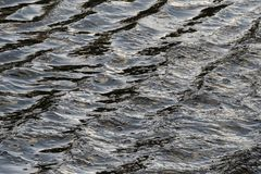 Waves in the surface of the water. Which result in a specific colour and structure Stock Photo