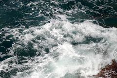 Waves that swell on the rocky t. Waves that swell on the rocky shores royalty free stock images