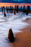 Waves swirl around pier pilings in the Delaware Bay at sunset, s Royalty Free Stock Photography