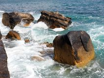 Waves Swirling Around Sandstone Rocks, Manly, Australia. Pacific Ocean waves breaking and swirling around large Sydney sandstone rocks at the waters edge, Manly Stock Photography