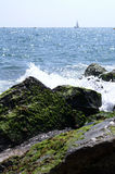 Waves threw ashore. Sea splashing onto stones with moss rocks & a cutter in the background royalty free stock photos