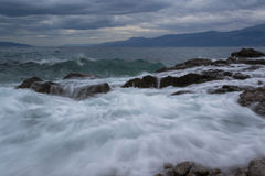 Waves to the left. Restless Waves of Adriatic Sea splashing on The Sea Rocks and going to the left site of The Beach, photographed in Rijeka, Croatia, at Winter stock image