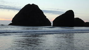 Waves With Two Large Rocks Off Shore Silhouetted. Two Large Rocks Silhouetted Against Sky With Waves stock video footage