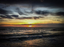 Waves under a sunset sky. A view of the sun setting over the ocean Stock Images