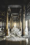 Waves under wooden pier Stock Images