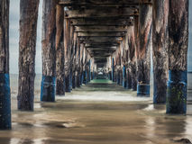 Waves underneath a Pier or Jetty on an Overcast Day royalty free stock image