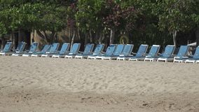 Waves of the warm sea run on the sandy beach of the tropical resort with umbrellas and chaise lounges.  stock video