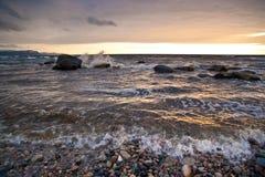 Waves wash ashore at sunset Stock Images