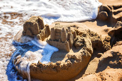 Waves wash away sand castles on beach the sea Stock Image