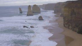 Waves wash onto shore near the Twelve Apostles. Australia stock footage
