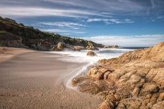 Waves wash onto a small sandy cove near Calvi in Corsica Stock Photo