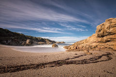 Waves wash onto a small sandy cove near Calvi in Corsica Royalty Free Stock Images
