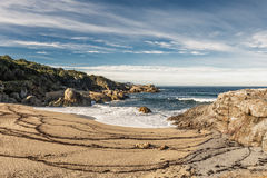 Waves wash onto a small sandy cove near Calvi in Corsica Stock Images