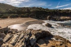 Waves wash onto a small sandy cove near Calvi in Corsica Stock Photos