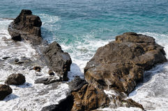 Waves wash over rocks Royalty Free Stock Images