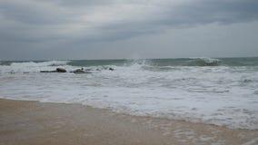 Waves wash the sandy shore. Ridge is broken on the rocks stock video footage