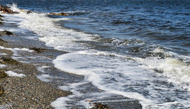 Waves washing ashore in Penobscot Bay, Maine. View of waves washing ashore on Penobscot bay in Searsport Maine in the spring Stock Photo