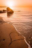 Waves washing a heart drawn on the beach sand away Stock Image