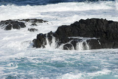Waves, water crashing into rocks in the sea. Rough seas causing waves to crash into rocks just off the coast of The Nobbies, Phillip Island, Victoria, Australia Stock Photos