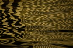 Waves on water create freakish diffractional structures similar. To velvet on its surface, yellow gold reflections on water organized into strict and chaotic stock photography